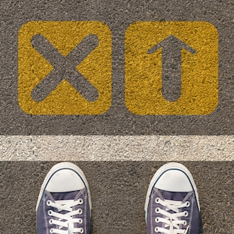 Pair of shoes standing on a road with two yellow arrow