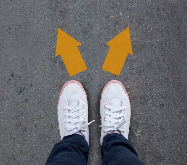 Pair of shoes standing on a tarmac road with two arrows