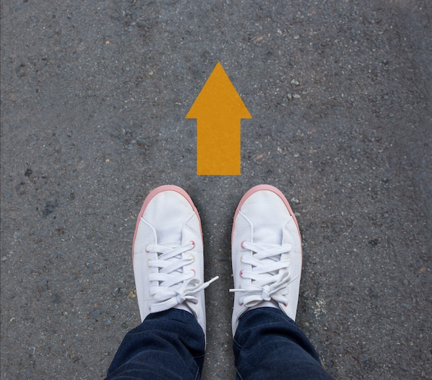 Pair of shoes standing on a tarmac road with yellow arrow