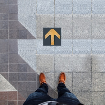 Pair of shoes standing with yellow arrow