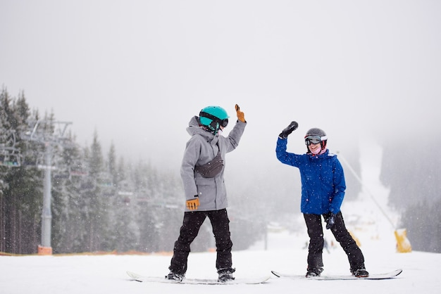 Pair of snowboarders giving high five standing on ski run with chairlift