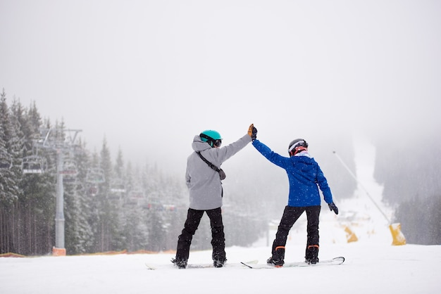 Pair of snowboarders with giving high five standing on ski run. dense foggy views in snowfall on background