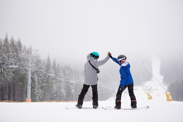 Pair of snowboarders with giving high five standing on ski slope