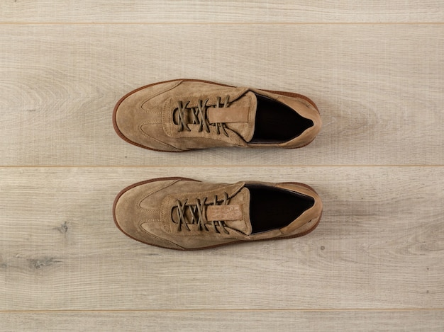 A pair of soft suede sneakers on a background of a plank surface close-up