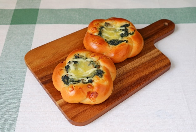 Pair of spinach and cheese buns on a wooden tray