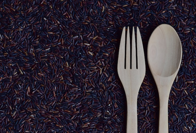 A pair of spoon and fork on riceberry (rice berry) which is a registered rice variety from