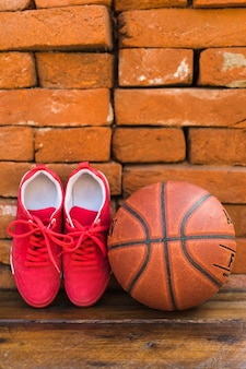 Pair of sport shoes and basketball on wooden table against stack of brick wall