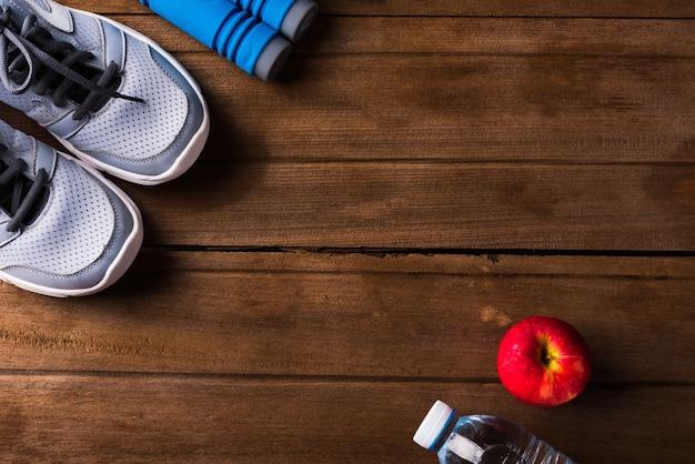 Соедините спортивную обувь, воду в бутылке, яблоко и скакалку на деревянном столе