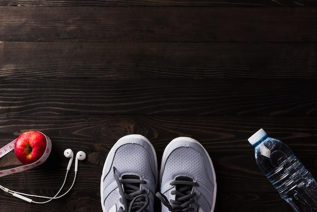 Соедините спортивную обувь, наушники, яблоко и бутылку с водой на черном деревянном столе