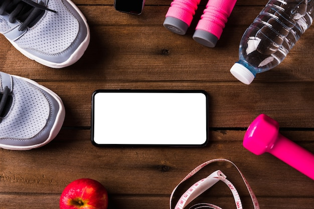 Пара спортивная обувь водное яблоко скакалка и пустой экран смартфона