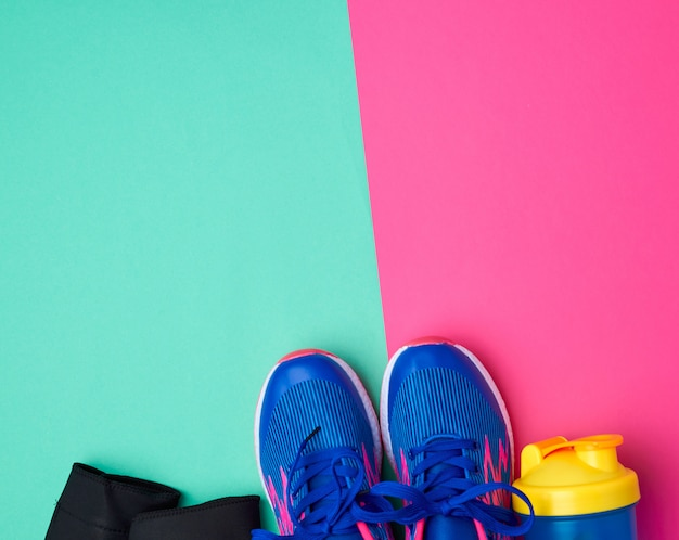Pair of sports sneakers with blue laces on a colored abstract background