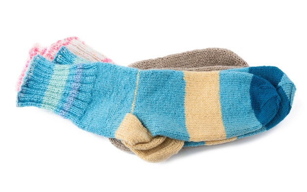 Pair of striped handmade knitted warm socks made of sheepã¢â€â™s wool yarn, clothing is isolated on a white background