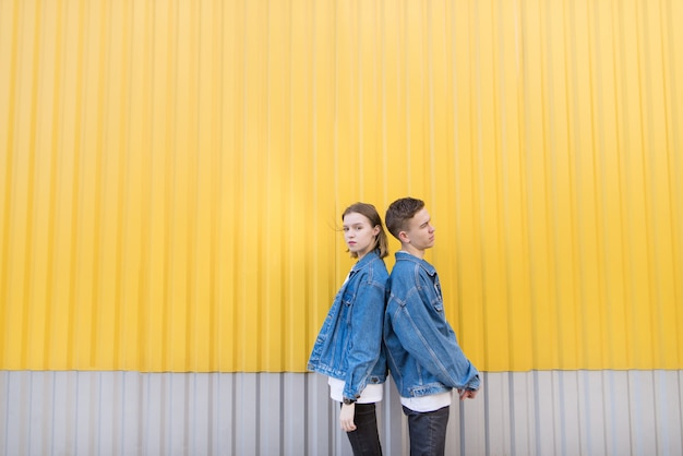 Pair of stylish people standing backs against background of yellow wall. hipsters photo.