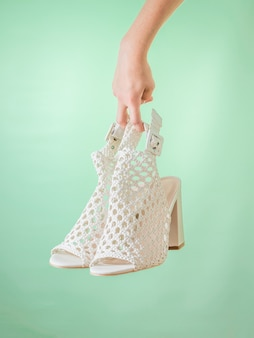 A pair of summer women's white shoes in hand on a green background. summer leather shoes for women.