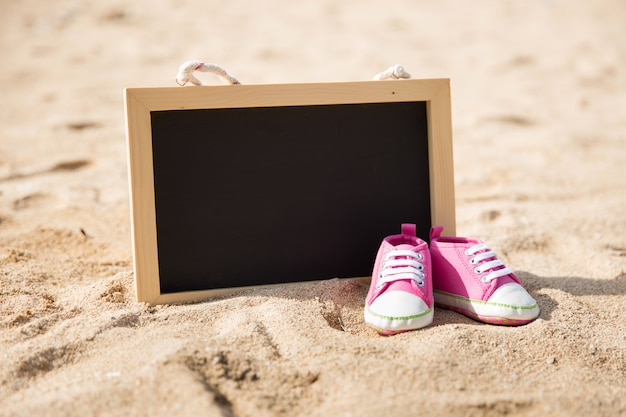 Pair of toddler shoes and mini chalk board on the sand
