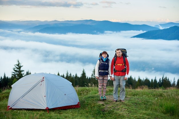 Pair of tourists with backpacks near the tent on the blurred background of the mighty mountains on which lies the fog. concept of a healthy lifestyle