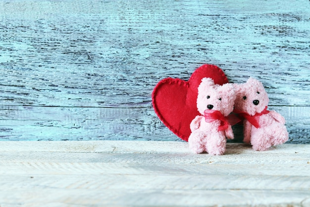 A pair of toys teddy bears on the background of a big red heart
