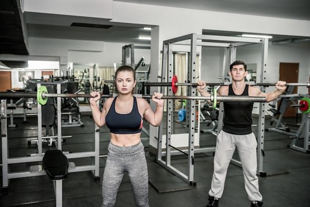 トレーニングインストラクターと女性のペア、両方ともダンベルを持っています