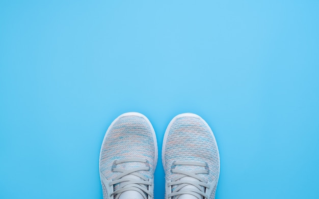 Pair of trendy sport sneakers on light blue background.