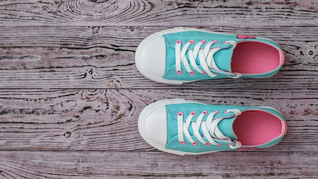 A pair of turquoise sneakers on a textured wooden floor.