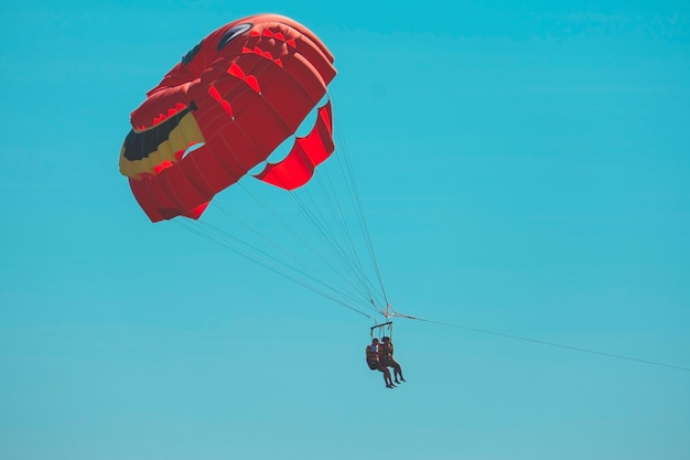 Pair of unrecognizable people on a parachute against a blue sky