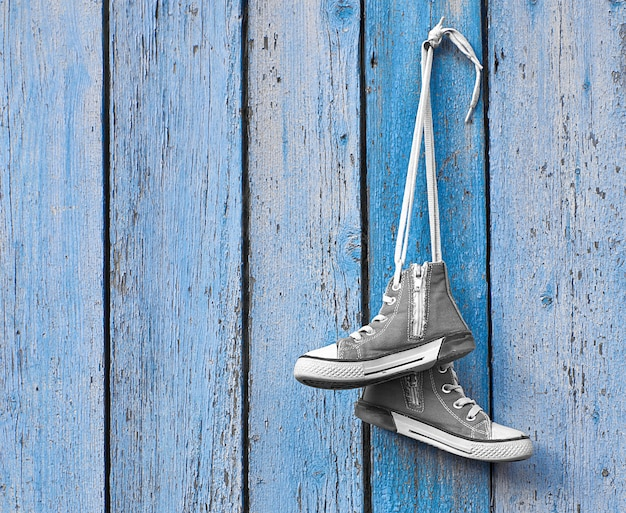 Pair of used textile shoes hang on a blue