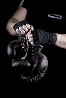 Pair of very old boxing sports gloves in men's hands