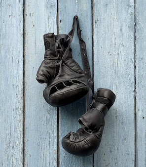 Pair of very old leather black boxing gloves hanging on a nail