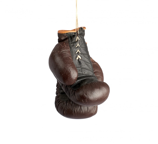 Pair of very old vintage brown leather boxing gloves hanging on a rope