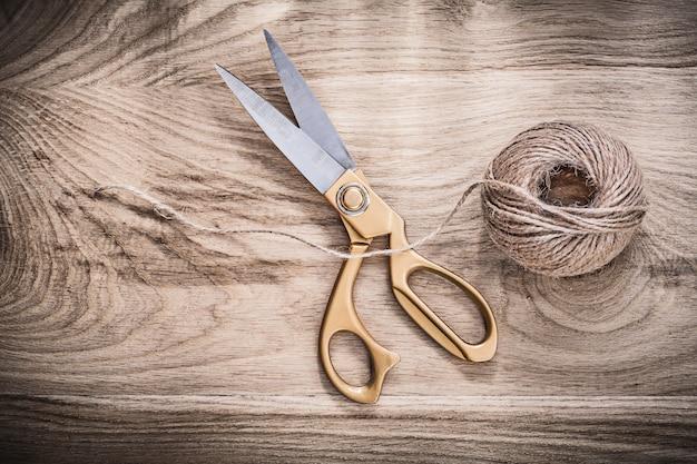 Pair of vintage golden scissors rope on wooden board