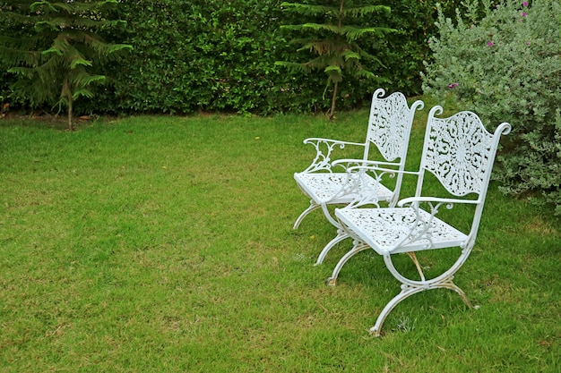 Pair of vintage style white colored wrought iron chairs in the vibrant green garden