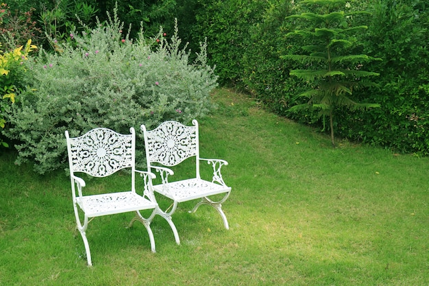 Pair of vintage style white wrought iron chairs in the green garden