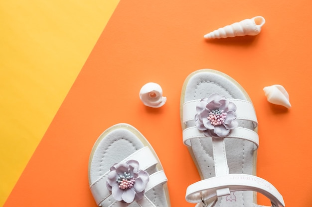 Pair of white baby sandals on color background top view.stylish leather girls sandals and seashells