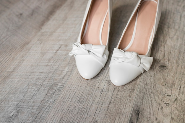 Pair of white dress shoes with bow on wooden textured background