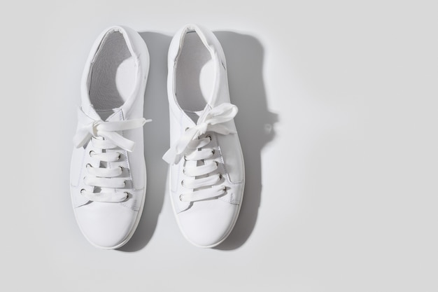 Pair of white female sneakers on yellow flat lay top view minimal background magazine concept