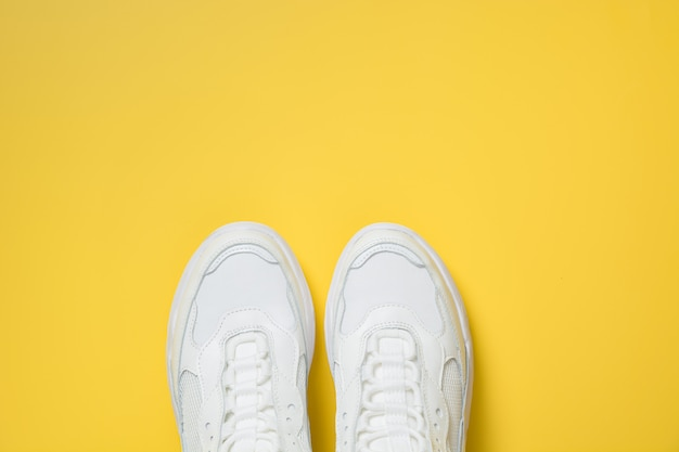 Pair of white female sneakers on yellow. flat lay, top view minimal.