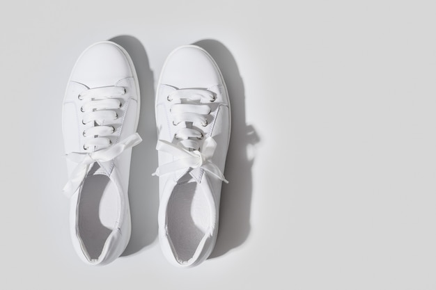 Pair of white female sneakers on yellow