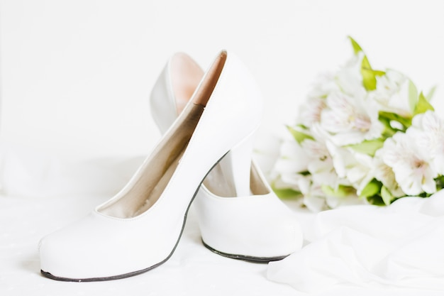 Pair of white high heels with scarf and flower bouquet on white backdrop