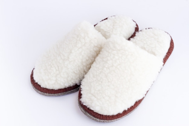 A pair of white home cozy slippers made of wool on a white surface