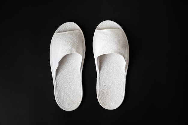 Pair of white house slippers on black background. top view of disposable slippers in dark contrasty background