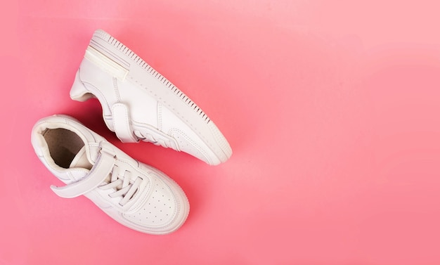Pair of white leather sneakers isolated on pink background.