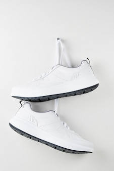 Pair of white male sneakers hanging on wall. fashion stylish sport shoes, close up
