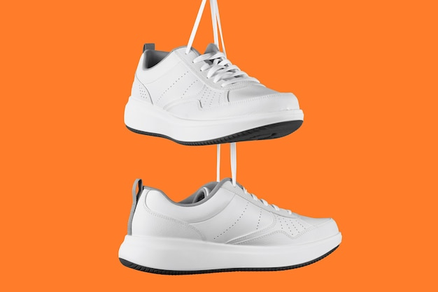 Pair of white male sneakers on orange background. stylish shoes isolated
