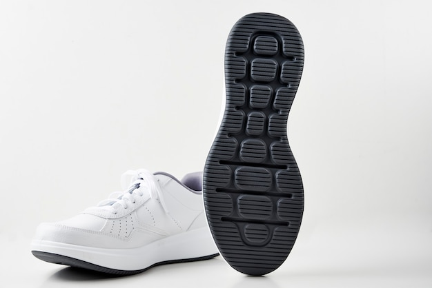 Pair of white male sneakers on a white background isolated.