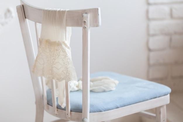 Pair of white nylon stockings hang on back of chair.