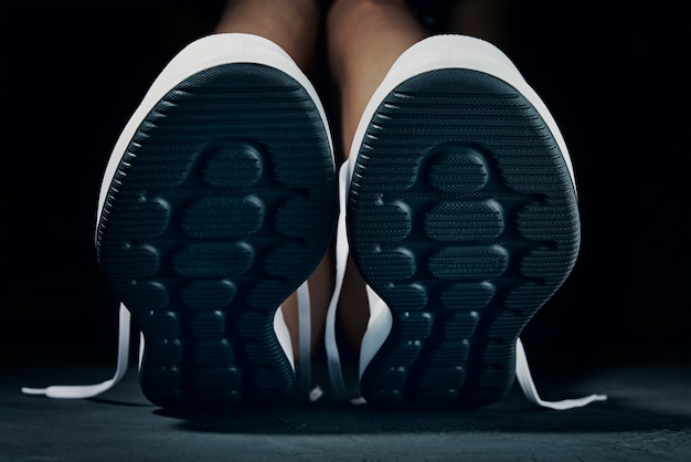 Pair of white sneakers isolated on black