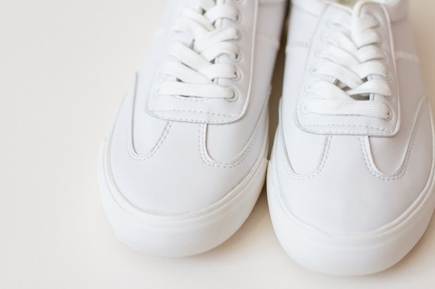 Pair of white sneakers shoes on white