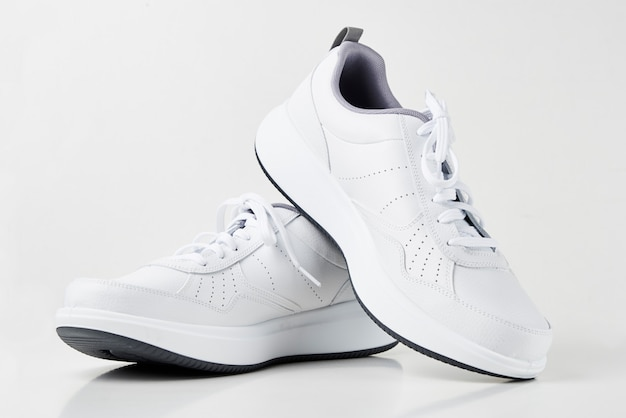 Pair of white sneakers on a white background