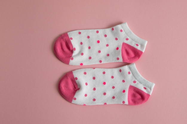 A pair of white socks for children with pink socks and heels, with pink dots,