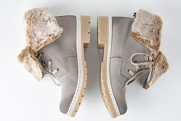 Pair of winter womens boots on white wall isolated, top view